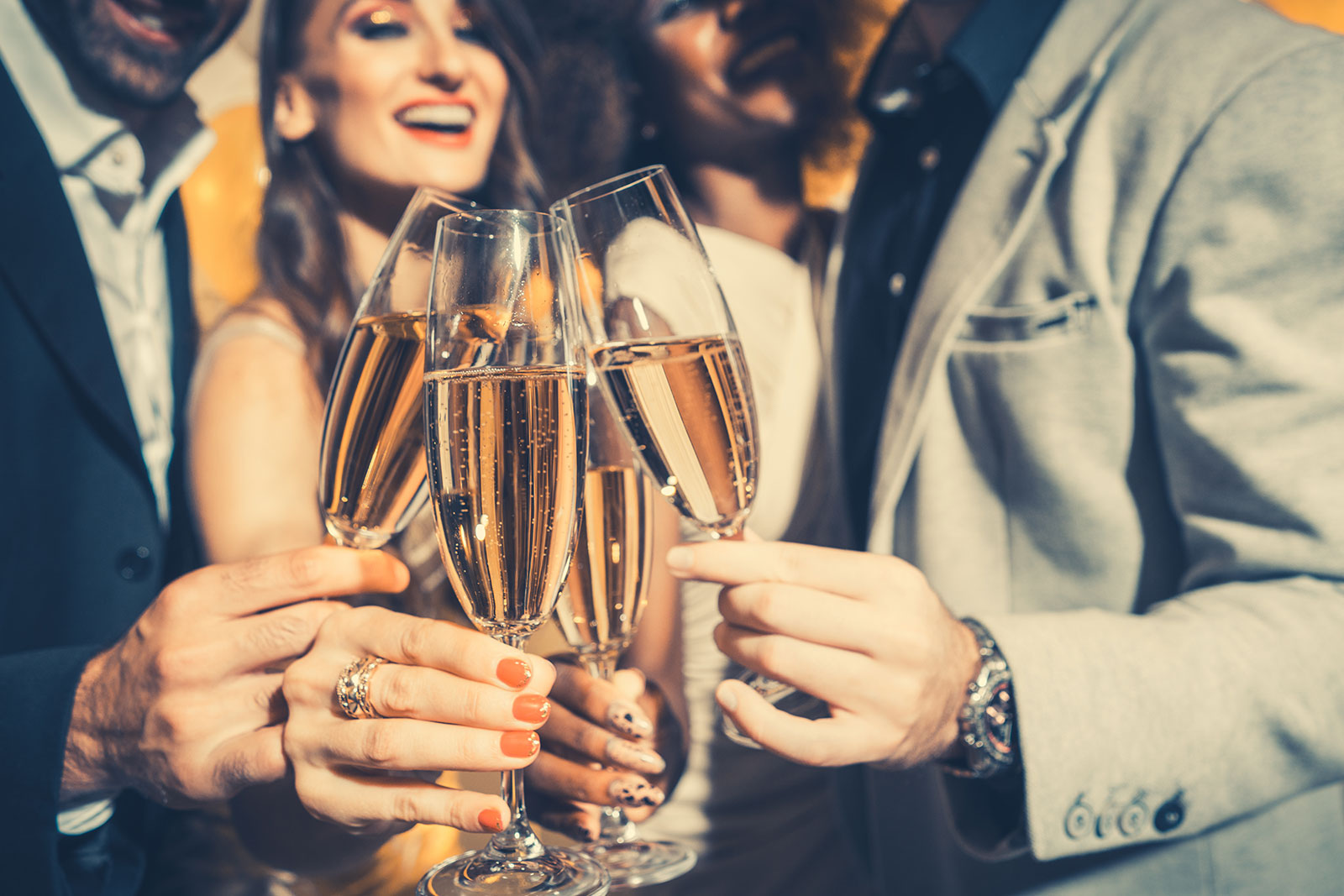 people celebrating holiday clinking glasses filled with champagne