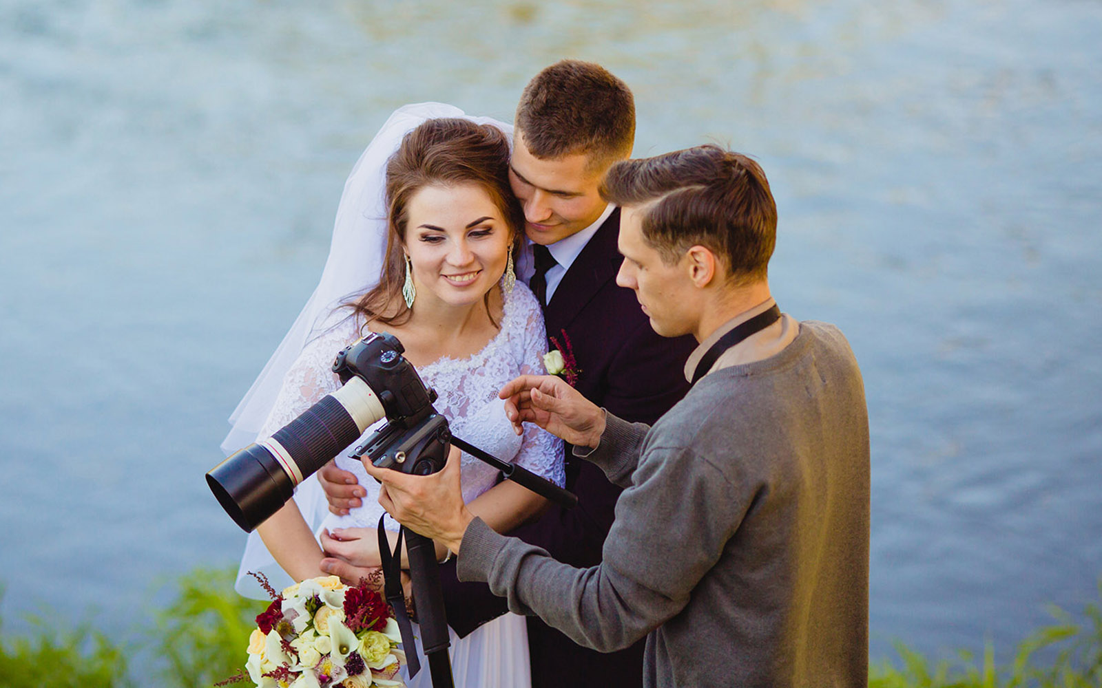 Wedding photographer reviewing photos with bride and groom